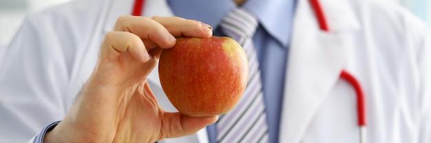 Männliche medizin therapeut therapeut hände halten roten frischen reifen apfel. medizinische hilfe oder versicherungskonzept. gesundheitsleben und gesundes lebensmittelkonzept. vegetarisches lebensstilkonzept. früchte und vitamine