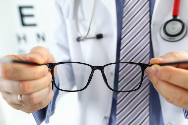 Männliche medizinarzthände, die dem patienten eine schwarze brille geben. sehtest und korrektur ausgezeichnete sicht laser-chirurgie alternative fahrer gesundheitszertifikat prüfung konzept