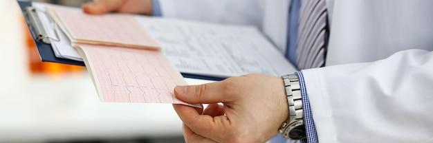 Männliche medizinarzthände, die kardiogramm-diagramm auf zwischenablageblock-nahaufnahme halten. der assistenzarzt des herztherapeuten macht das konzept der herzrhythmusstörung zur messung der herzrhythmusstörung