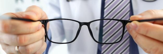 Männliche medizinarzthände geben eine schwarze brille