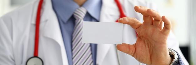 Männliche medizinarzthand, die leere visitenkarte hält. arzt, der weiße visitenkarte in kamera-nahaufnahme zeigt. konzept des kontaktinformationsaustauschs. einführung der geste bei einem formellen treffen