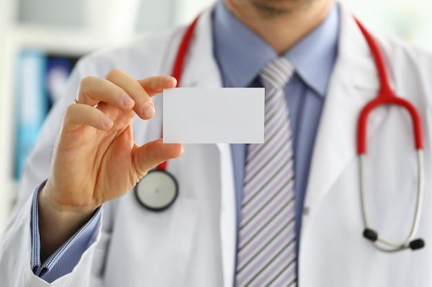 Männliche medizinarzthand, die leere visitenkarte hält. arzt zeigt weiße visitenkarte. konzept des kontaktinformationsaustauschs. einführung der geste bei einem formellen treffen
