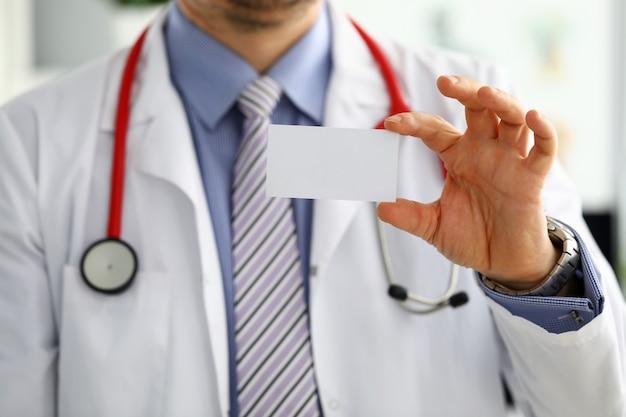 Männliche medizinarzthand, die leere visitenkarte hält