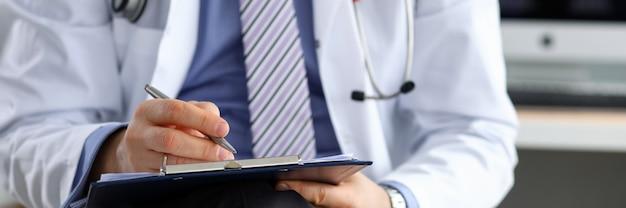 Männliche medizinarzthand, die silbernen stift hält, der etwas auf zwischenablage-nahaufnahme schreibt. stationsrunde, patientenbesuchscheck, medizinische berechnung und statistikkonzept. arzt bereit, patienten zu untersuchen