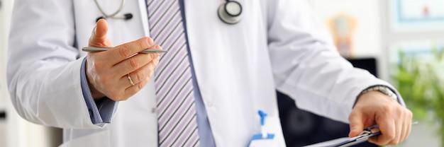 Männliche medizinarzthand, die silbernen stift hält