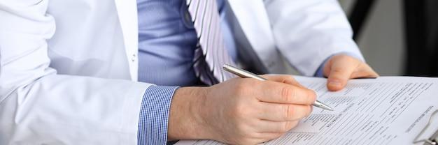 Männliche medizinarzthand, die silberstiftschrift hält