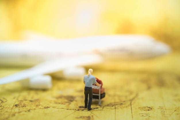 Männliche miniaturfigur mit flughafenwarenkorb und gepäck auf weltkarte mit flugzeugmodell.