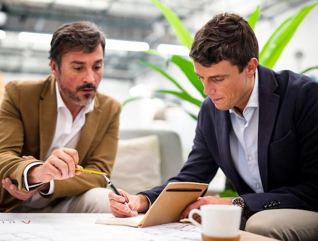 Männliche mitarbeiter des niedrigen winkels, die im büro sich treffen
