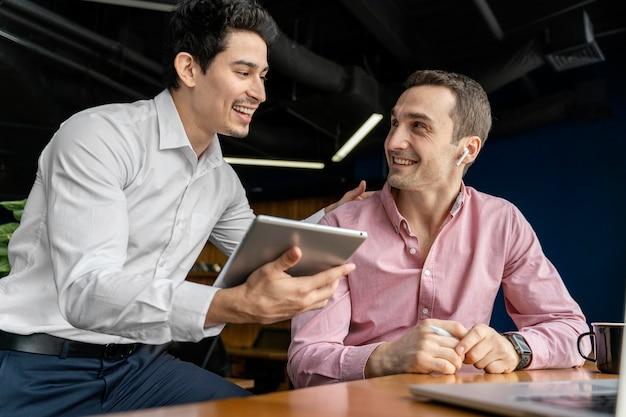 Männliche mitarbeiter von smiley, die sich bei der arbeit unterhalten