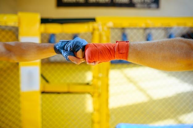 Männliche mma-kämpferhände mit roten und blauen bandagen im innenraum des fitnessraums