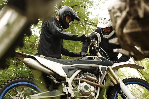Männliche motorradfahrer in helmen bereiten motorrad für waldrennen vor oder überprüfen es nach herbst