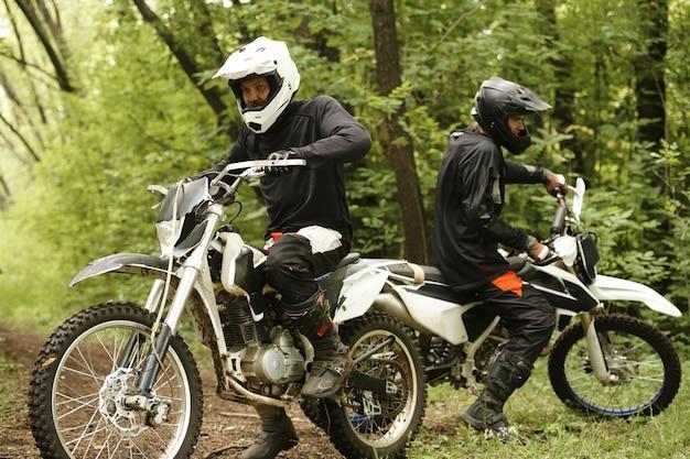 Männliche motorradfahrer in helmen, die auf motorrädern sitzen und sich darauf vorbereiten, im wald abzubiegen