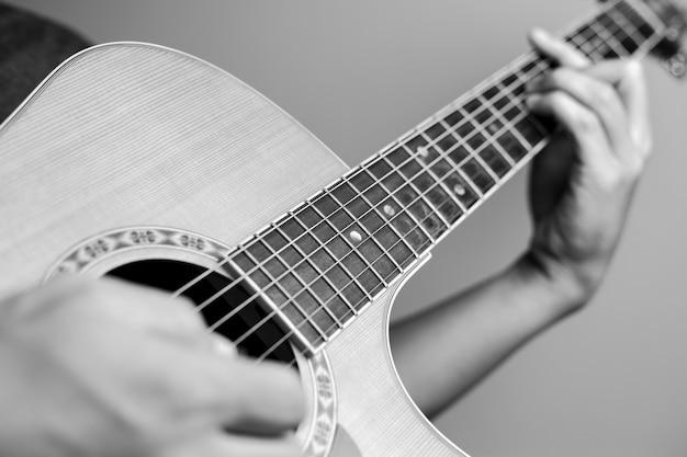 Männliche musiker, die akustische gitarre spielen. nahaufnahmemusiker spielen akustische gitarre. männliche musiker halten akkorde und schlaggitarre.