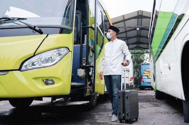 Männliche muslime reisen mit dem öffentlichen bus während der pandemie, die maske trägt