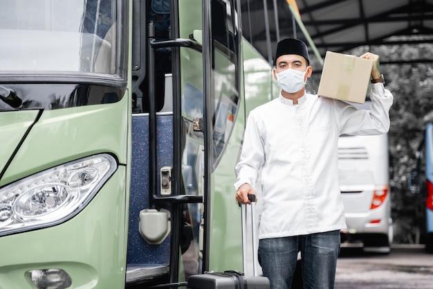 Männliche muslime reisen mit dem öffentlichen bus während der pandemie tragenden maske