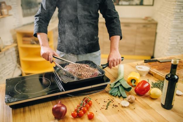 Männliche person, die fleisch in einer pfanne auf der küche kocht