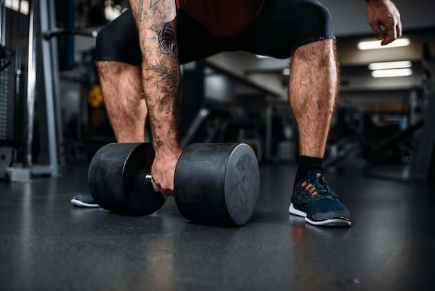 Männliche person, die übung mit hantel, training im fitnessstudio macht.