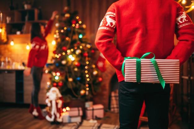 Männliche person hält ein geschenk hinter seinem rücken, weihnachten.