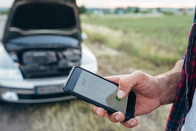 Männliche person hand mit telefon, kaputtes auto mit offener motorhaube. problem mit fahrzeug, notdienst