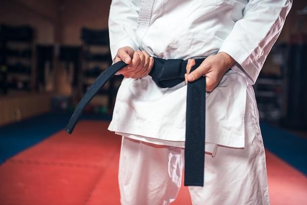 Männliche person im weißen kimono mit schwarzem gürtel