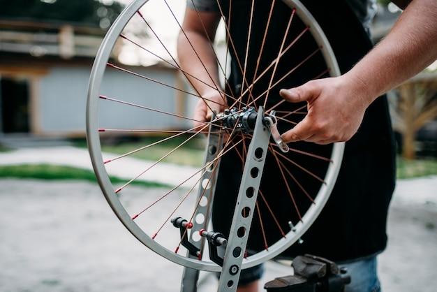 Männliche person in schürze stellt fahrradspeichen und rad mit servicewerkzeugen ein.