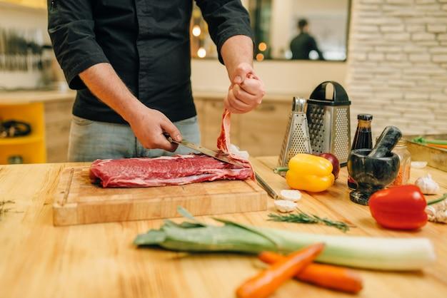 Männliche person mit messer schneidet rohes fleisch auf holzbrett