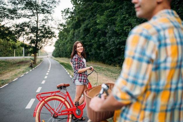 Männliche person und junge frau, die auf retro-fahrrädern reiten. paar auf vintage-fahrrädern. junger mann und frau auf alten zyklen, romantisches date