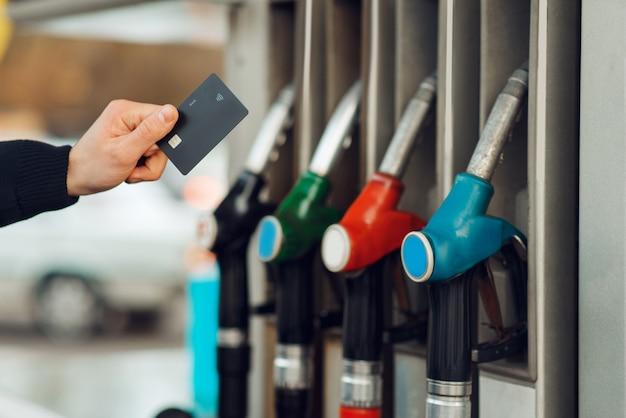Männliche personenhand nimmt die pistole auf tankstelle, nahaufnahme, kraftstofffüllkonzept. benzintanken, benzin- oder dieseltankservice