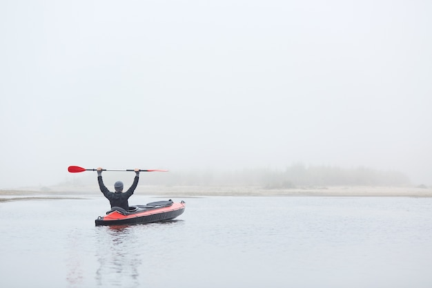 Männliche polsterung in flusspolsterung, sitzen im kanu mit angehobenem paddel, wassersport und schöne natur genießend, schwarze jacke und graue mütze tragend