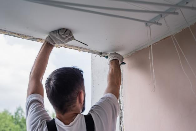 Männliche prozessarbeitskraft, die oben fenster in einem haus, abschluss repariert