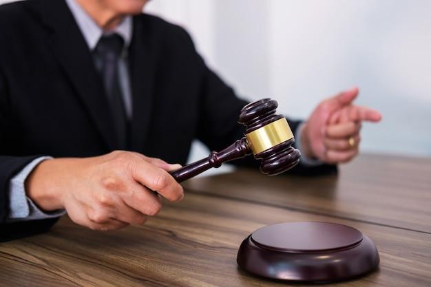 Männliche rechtsanwalt- oder richterhand schlägt den hammer auf klingendem block und arbeitet am gerichtssaal