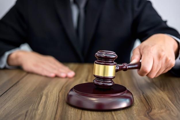 Männliche rechtsanwalt- oder richterhand schlägt den hammer auf klingendem block