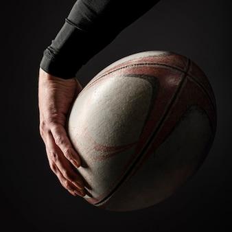 Männliche rugbyspielerhand, die ball hält