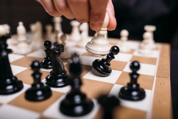 Männliche schachspielerhand, die weiße figur, nahaufnahme hält.