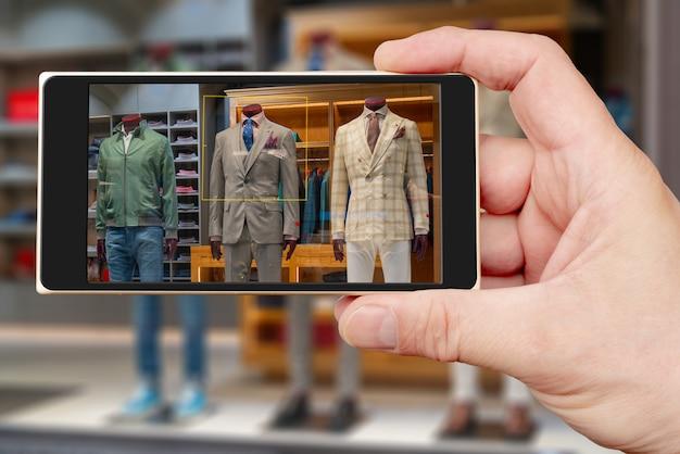 Männliche schaufensterpuppe auf dem smartphonebildschirm. verkauf von herrenbekleidung. showcase bekleidungsgeschäft.
