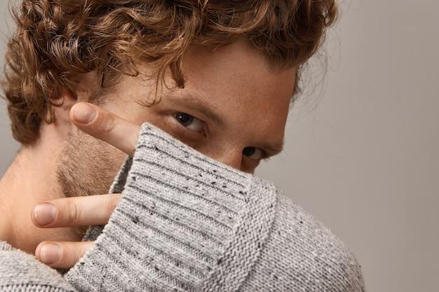 Männliche schönheit, stil und modekonzept. nahaufnahme des geheimnisvollen gutaussehenden jungen mannes mit lockigem haar, schönen magnetischen augen, seine finger ragen aus grauem gestricktem ärmel heraus