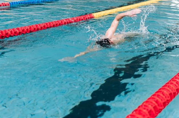 Männliche schwimmen des hohen winkels im becken