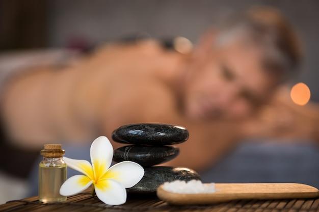 Männliche spa-einstellung mit schwarzen heißen steinen