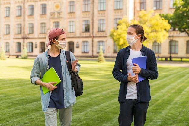 Männliche studenten, die auf dem campus kontakte knüpfen