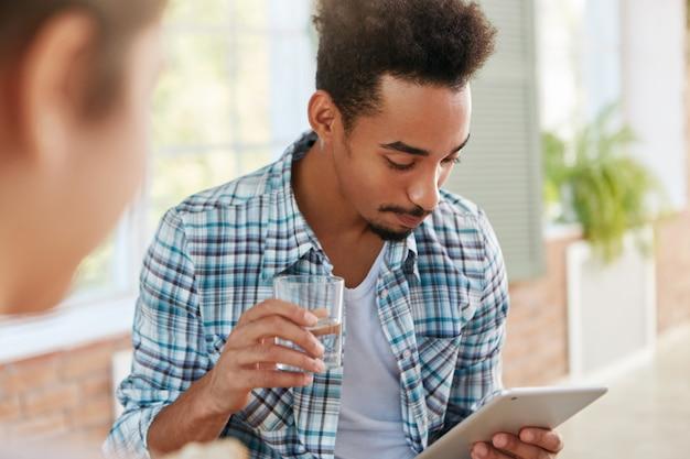 Männliche studenten gemischter rassen haben eine frist für die vorbereitung auf die abschlussprüfung und suchen im internet nach antworten