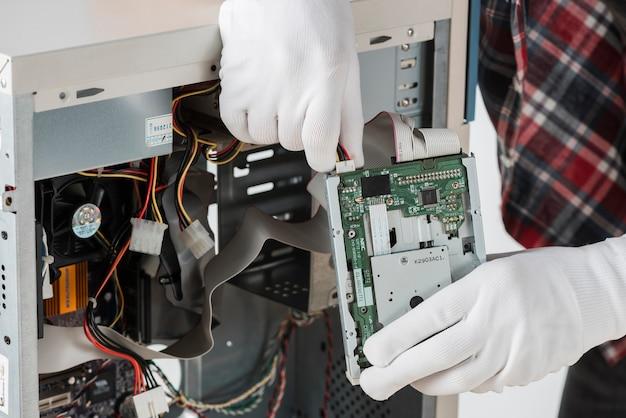 Männliche technikerhand, die festplattenlaufwerk des computers repariert