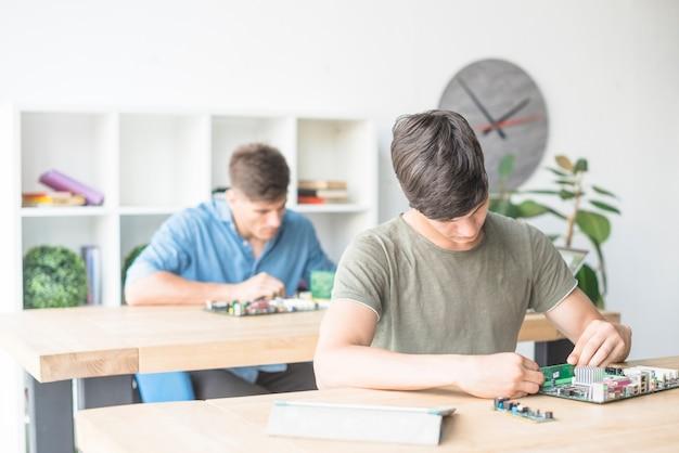 Männliche technikerstudenten, die motherboard in der service-center reparieren