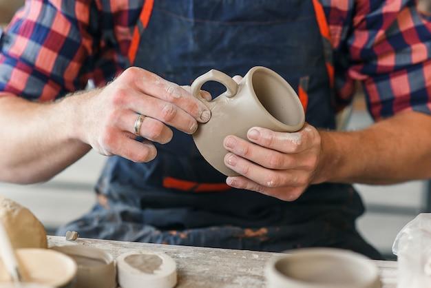 Männliche töpferhände, die keramikkappe in der keramik machen.