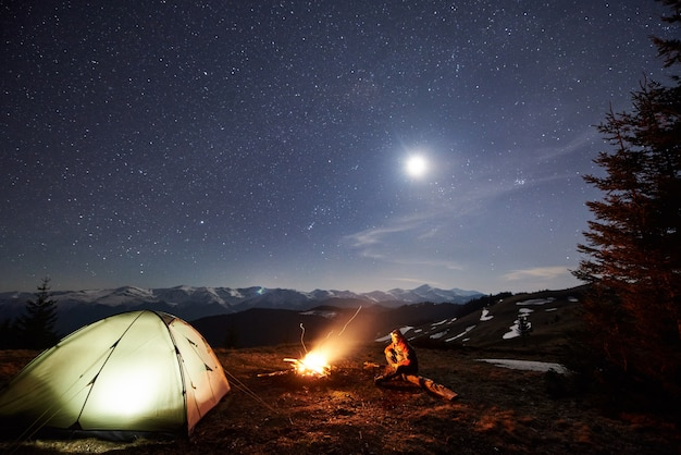 Männliche touristen ruhen sich nachts in seinem lager in der nähe des waldes aus.