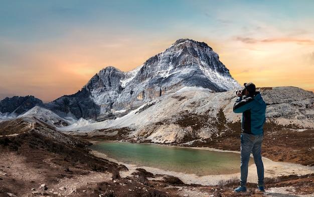 Männliche touristen stehen am schneeberg und am fünffarbigen see (wuse hai) im yading-nationalreservat, landkreis daocheng, provinz sichuan, china.