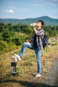 Männliche touristen trinken wasser und füße traten auf kilometer.