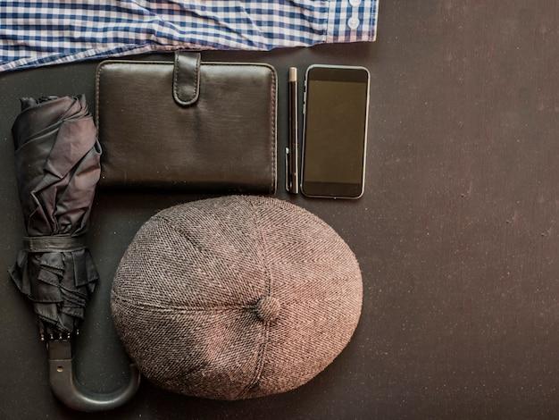 Männliche traditionelle sachen der flachen lage am dunklen oberflächennotizbuchregenschirmtelefon und -hut