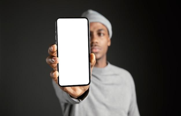 Männliche tragende kappe, die telefon hält