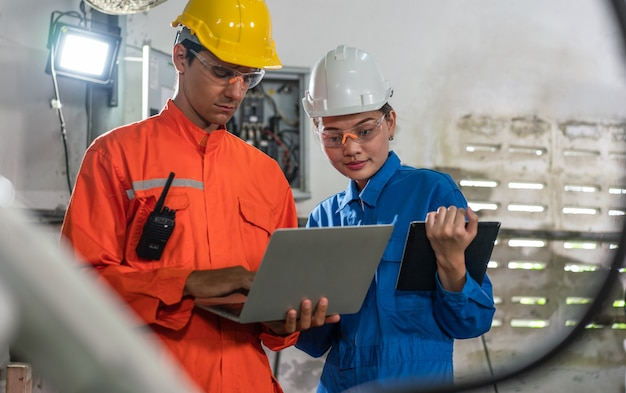 Männliche und weibliche automatisierungsingenieure tragen eine uniform mit helmsicherheitsinspektion, steuern eine roboterarmschweißmaschine mit einem laptop in einer industriefabrik. konzept der künstlichen intelligenz.
