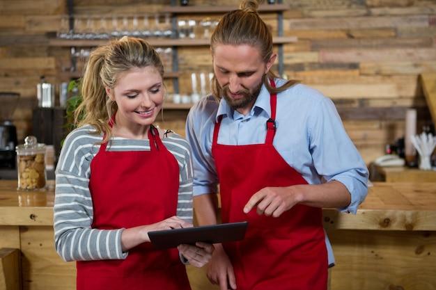 Männliche und weibliche baristas, die digitales tablett im coffeeshop verwenden